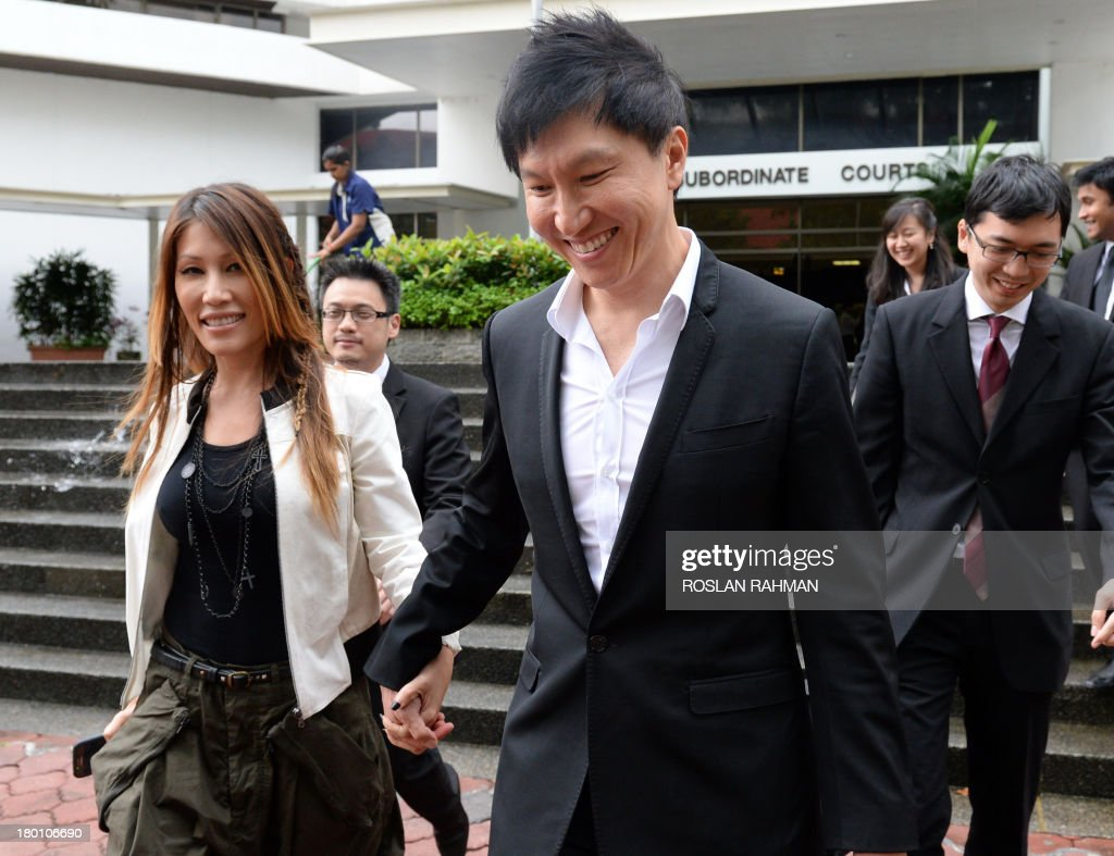 City Harvest Church founder Kong Hee (C) walks out for a lunch break with his pop-singer wife Ho Yeow Sun (L) during his trial at the subordinate courts in Singapore on September 9, 2013. The trial continues for the leaders of a Singapore-based Christian church accused of embezzling millions of dollars to finance the singing career of the pastor's wife.
