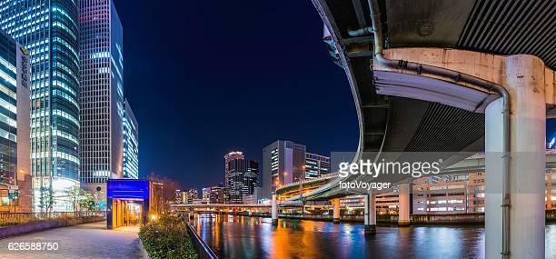 City highway curving through modern skyscrapers illuminated night Osaka Japan