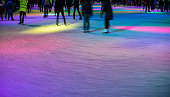 Skaters on a ice rink in colorful lights at evening. Copy space.