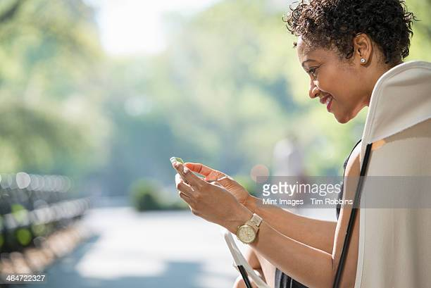 City life. A woman sitting in a camping chair in a city park, checking her cell phone.