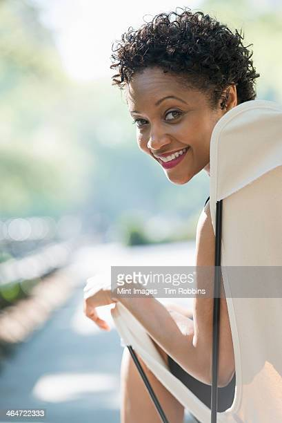 City life. A woman sitting in a camping chair in a city park, smiling and looking over her shoulder.