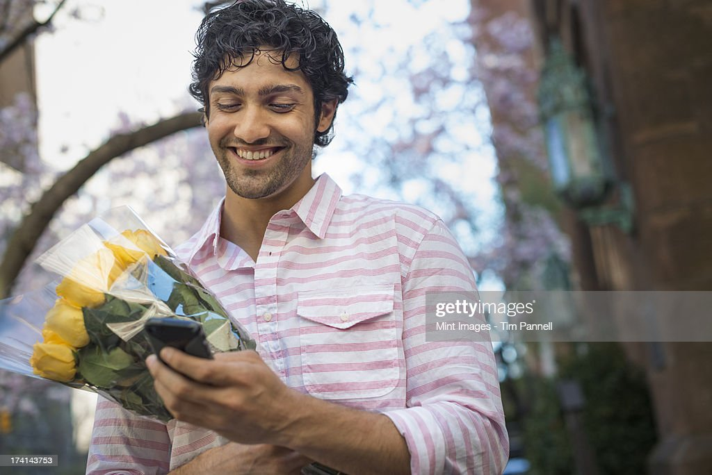 City life. A young man in the park in spring, using a mobile phone.  Holding a bunch of yellow roses.  : Stock Photo
