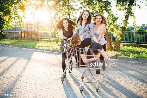 La ville: Femmes amis s'amusant avec un panier d'achats
