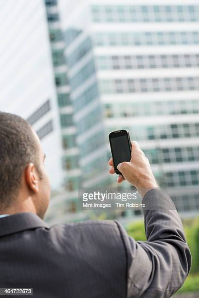 City life. People on the move. A man in a business suit holding his smart phone at arms length.