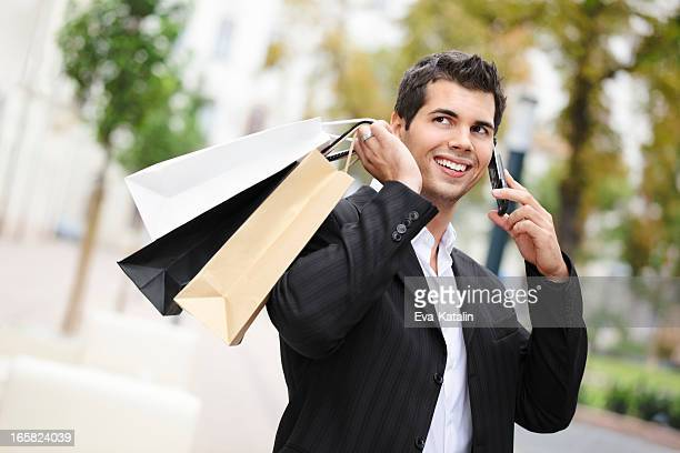 City life series: businessman on the phone holding shopping bags