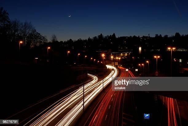 La vie urbaine avec de l'autoroute et de la lune sur l'horizon