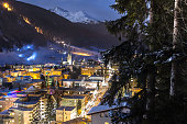 DAVOS, SWITZERLAND, CANTON GRISONS city night panorama in winter of the city and jakobshorn covered with snow. Winter ski sports resort and home of the WORLD ECONOMIC FORUM every january