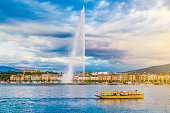 Beautiful view of Geneva skyline with famous Jet d'Eau fountain at harbor district in beautiful evening light, Switzerland.