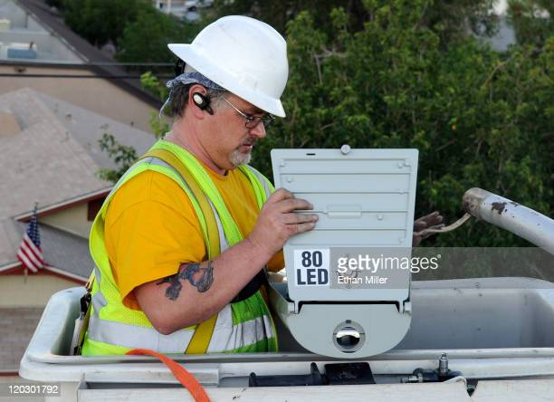City of Las Vegas field electrician John Meier replaces a streetlight with a new LED fixture August 3 2011 in Las Vegas Nevada The 6600 new...