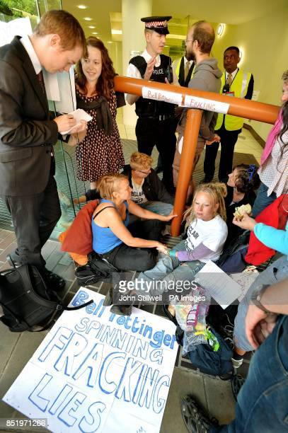 A City of London Police officer talks to s spokesman for a group of antifracking demonstrators as they sit with their hands superglued to each other...