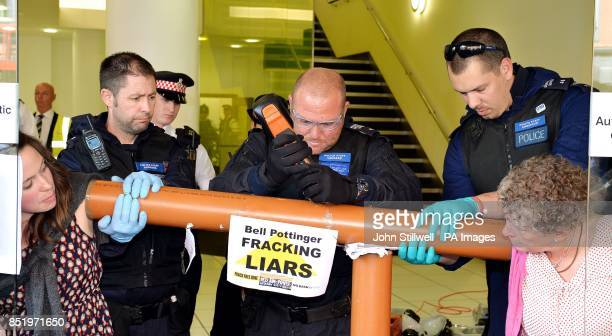 A City of London Police officer uses an oscillator to cut a hole in a plastic pipe to unglue their hands that were superglued to each other in an...