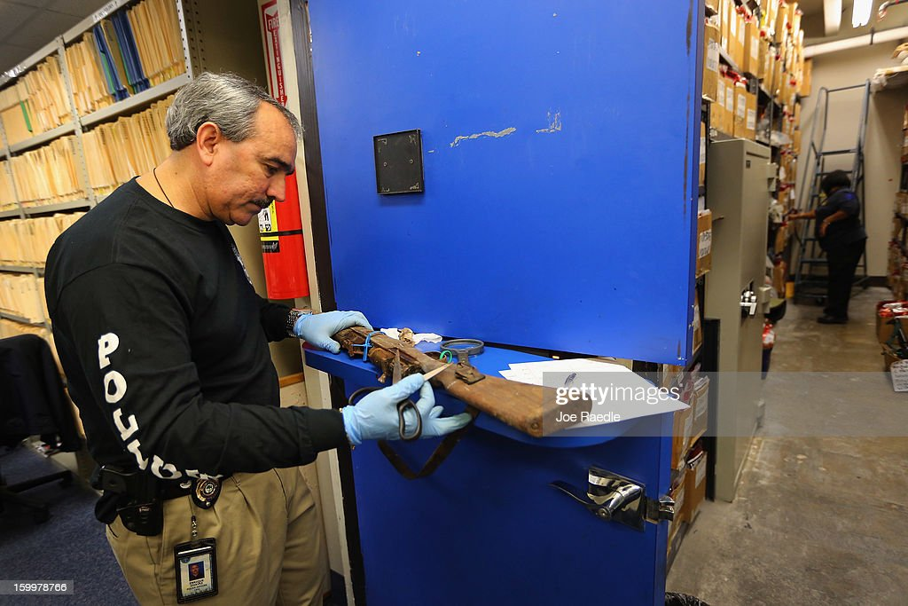 City of Miami Police Homicide/Gun Squad Detective Enrique Chavez looks for identifying marks on a weapon that was turned in during a recent gun buyback program as he logs the weapons at the Miami Police station on January 24, 2013 in Miami, Florida. As the Federal Government begins to grapple with the gun issue after recent mass shootings, Miami took in 130 guns during a recent gun buyback.