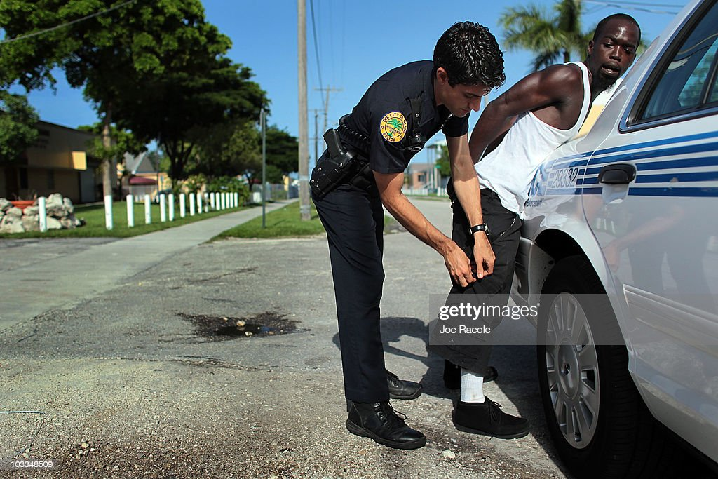 city of miami police officer eldys diaz searches a person before placing him into the back of. Black Bedroom Furniture Sets. Home Design Ideas