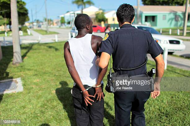 City of Miami police officer Eldys Diaz walks a handcuffed person to his patrol car while patrolling the streets on August 11 2010 in Miami Florida...