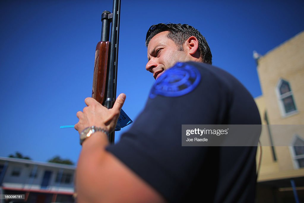 City of Miami police officer Freddie Cruz carries a 12 gauge shotgun that was turned in during a gun buy back event on January 26, 2013 in Miami, Florida. The event was the second one of the year in efforts to reduce gun violence, the first one brought in 130 guns.