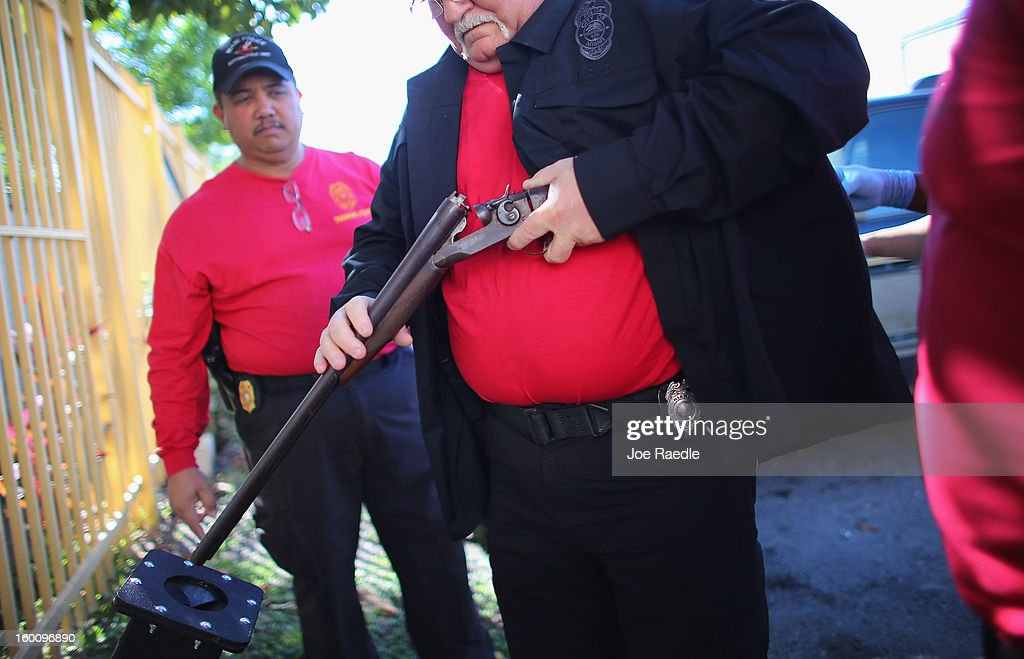 City of Miami police officer Robert Novo checks a shotgun that was turned in during a gun buy back event on January 26, 2013 in Miami, Florida. The event was the second one of the year in efforts to reduce gun violence, the first one brought in 130 guns.