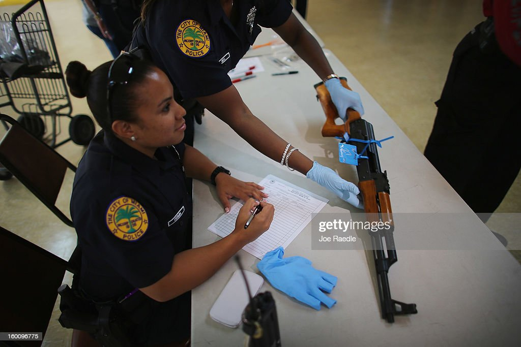 City of Miami police officers Angiee Fermin (L) and Michaelle Bell process an AK-47 that was turned in during a gun buy back event on January 26, 2013 in Miami, Florida. The event was the second one of the year in efforts to reduce gun violence, the first one brought in 130 guns.