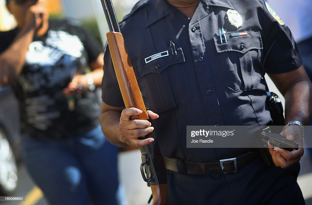 City of Miami police officers Kelvin Harris carries a handgun and rife that were turned in during a gun buy back event on January 26, 2013 in Miami, Florida. The event was the second one of the year in efforts to reduce gun violence, the first one brought in 130 guns.