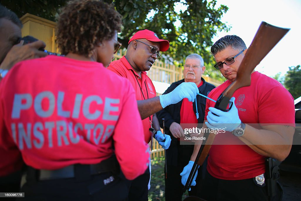 City of Miami police officers Walter Byars (L) and Luis Gonzalez take and process a weapon taken in during a gun buy back event on January 26, 2013 in Miami, Florida. The event was the second one of the year in efforts to reduce gun violence, the first one brought in 130 guns.