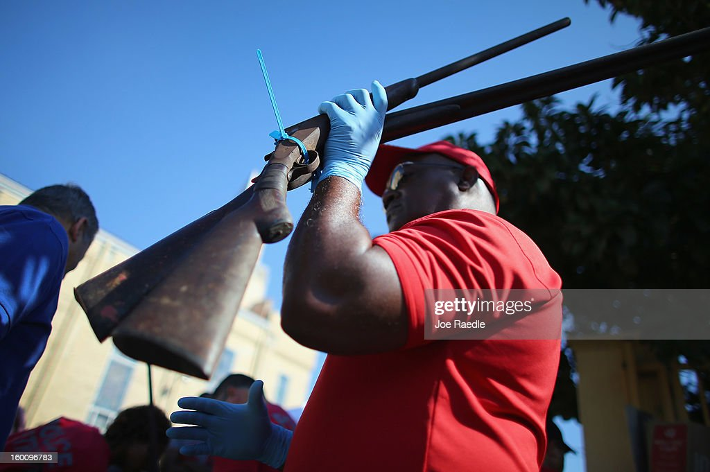 City of Miami police officers Walter Byars holds two weapons as he processes them during a gun buy back event on January 26, 2013 in Miami, Florida. The event was the second one of the year in efforts to reduce gun violence, the first one brought in 130 guns.