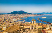 Scenic picture-postcard view of the city of Napoli (Naples) with famous Mount Vesuvius in the background in golden evening light at sunset, Campania, Italy.