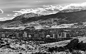 Landscape view of the City of Reno downtown area snow capped mountains and multiple casinos. This monochrome photograph from the foothills north of town looking southwest at the downtown area showing