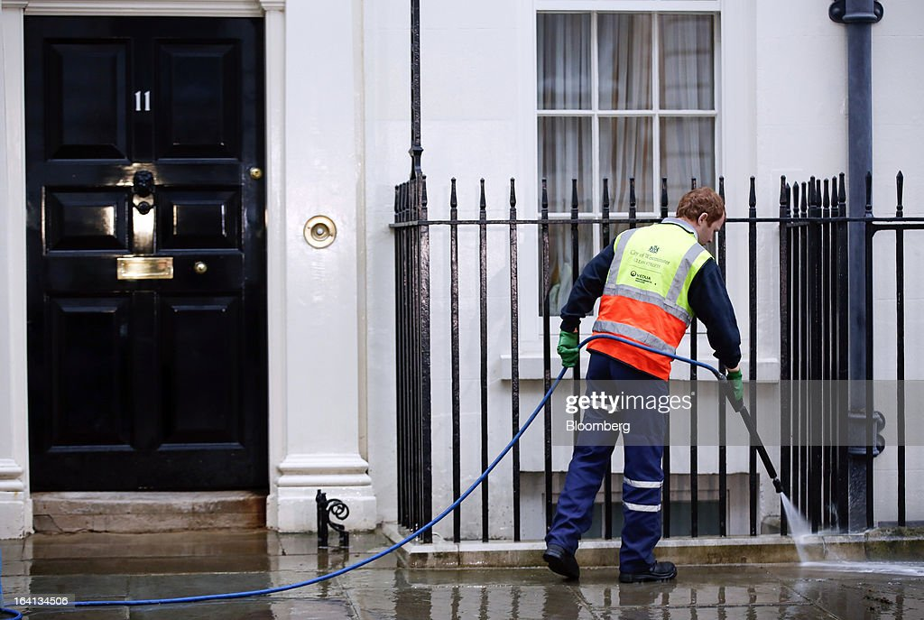 A City of Westminster council worker cleans the sidewalk outside 11 Downing Street, the U.K. residence of the chancellor of the exchequer, in preparation for his appearance with the dispatch box in Downing Street, London, U.K., on Wednesday, March 20, 2013. As many as 250,000 U.K. public-sector workers have been called out on strike today to protest cuts to their pay, pensions and working conditions to coincide with Chancellor of the Exchequer George Osborne's annual budget speech in Parliament. Photographer: Jason Alden/Bloomberg via Getty Images