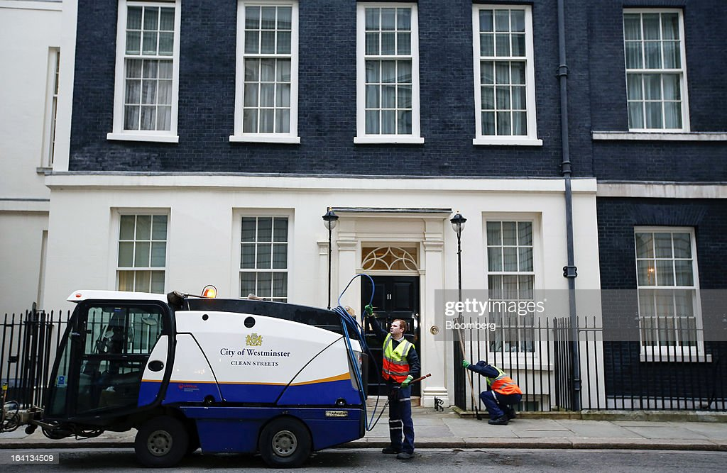 City of Westminster council workers clean the sidewalk outside 11 Downing Street, the U.K. residence of the chancellor of the exchequer, in preparation for his appearance with the dispatch box in Downing Street, London, U.K., on Wednesday, March 20, 2013. As many as 250,000 U.K. public-sector workers have been called out on strike today to protest cuts to their pay, pensions and working conditions to coincide with Chancellor of the Exchequer George Osborne's annual budget speech in Parliament. Photographer: Jason Alden/Bloomberg via Getty Images