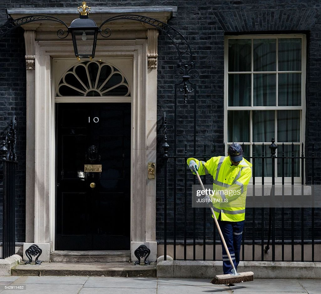 A City of Westminster worker sweeps the pavement outside 10 Downing Street in central London on June 25, 2016. The result of Britain's June 23 referendum vote to leave the European Union (EU) has pitted parents against children, cities against rural areas, north against south and university graduates against those with fewer qualifications. London, Scotland and Northern Ireland voted to remain in the EU but Wales and large swathes of England, particularly former industrial hubs in the north with many disaffected workers, backed a Brexit. / AFP / JUSTIN
