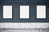 Row of three blank posters on an urban wall. Includes clipping path.