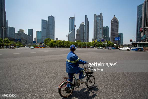 A city sanitation worker stops at a crossroad looking at the skyscrapers in Lujiazui Located in the Pudong New District on the eastern bank of...