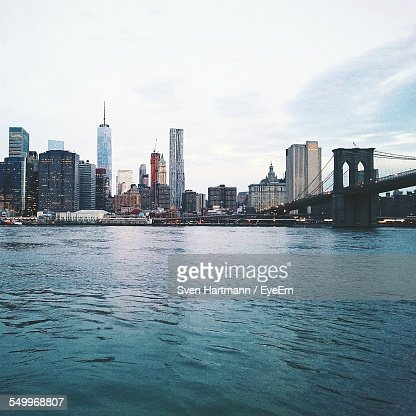City Skyline And Brooklyn Bridge By River Against Sky