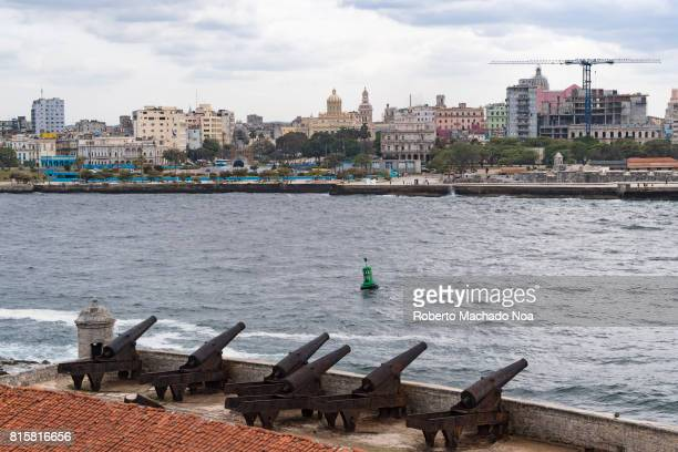City skyline from 'El Morro Castle' Row of old historic war cannons on stone rampart pointing towards a modern city with tall buildings across the sea