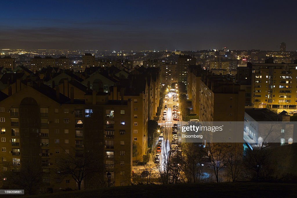 A city street and residential apartments stand illuminated by electric lighting in Madrid, Spain, on Friday, Jan. 4, 2013. In December, the Spanish parliament passed an energy law that imposed a 7 percent tax on electricity generation from Jan. 1 to plug the deficit. Photographer: Angel Navarrete/Bloomberg via Getty Images