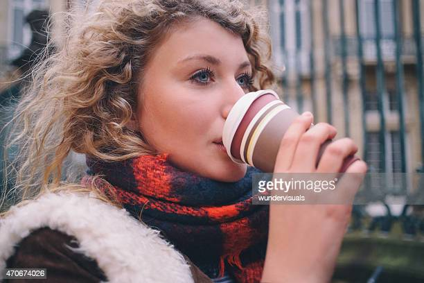 City student sipping a takeaway coffee on a winter day