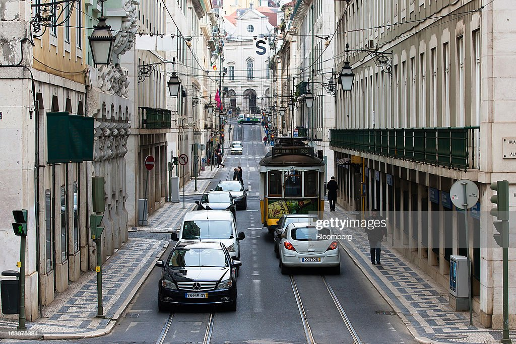 A city tram and automobiles pass along a shopping street in Lisbon, Portugal, on Saturday, March 2, 2013. Prime Minister Pedro Passos Coelho is battling rising joblessness and lower demand from European trading partners as he raises taxes to meet the terms of a 78 billion-euro ($104 billion) aid plan from the European Union and the International Monetary Fund. Photographer: Mario Proenca/Bloomberg via Getty Images
