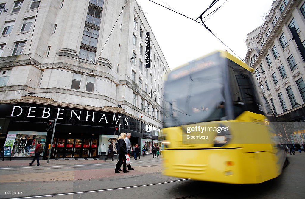 A city tram passes a Debenhams Plc department store in central Manchester, U.K., on Monday, April 1, 2013. U.K. retail sales unexpectedly stagnated in March in a sign that consumer spending remains under pressure from higher energy bills and weak wage growth. Photographer: Paul Thomas/Bloomberg via Getty Images