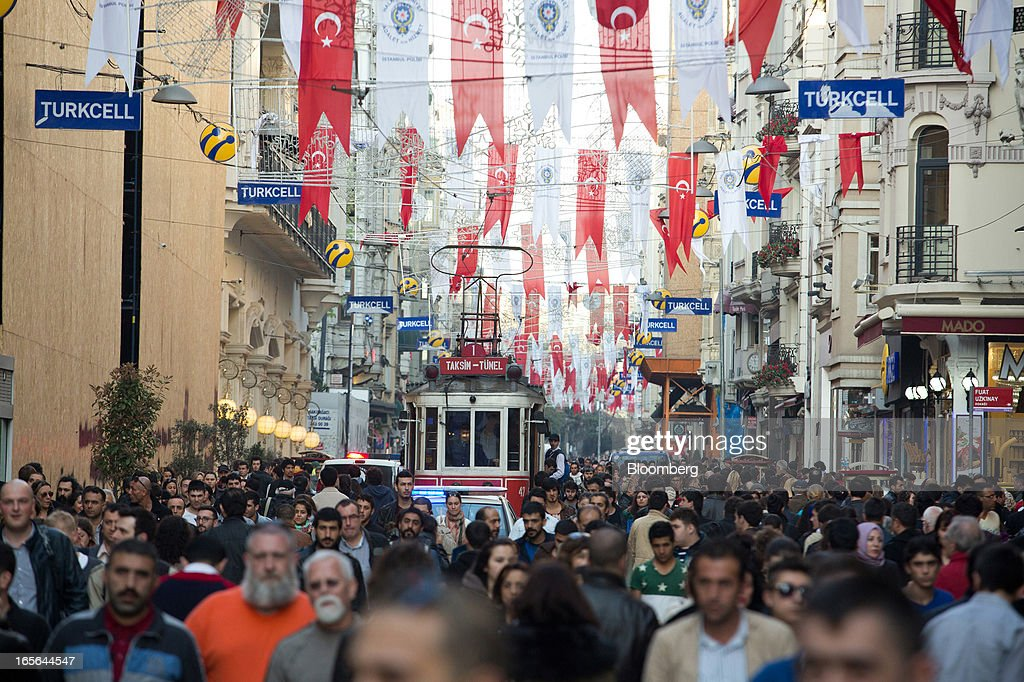 A city tram passes pedestrians walking along a busy street beneath Turkish national flags hanging from buildings in the Beyoglu district of Istanbul, Turkey, on Thursday, April 4, 2013. Turkey's gross domestic product expanded 2.2 percent in 2012, down from 8.8 percent the previous year, according to data released by the statistics office in Ankara on April 1. Photographer: Kerem Uzel/Bloomberg via Getty Images