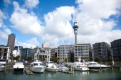 City View of Viaduct Harbour with motorboats luxury apartements the Skytower and the skyline on November 24 2010 in Auckland New Zealand