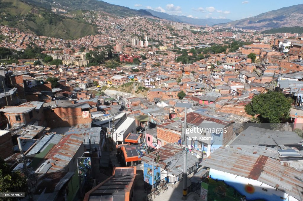 A city view with the covered escalators running in '20 de Julio' neighborhood in the Comuna 13 slums on January 5, 2013 in Medellin, Colombia. The stairway is divided into six sections and has a length of 1,260 feet. An escalator goes up and a second goes down.Residents used to climb hundreds of steps to get home from the bottom of the hill, but the journey now takes just 6 minutes. Comuna 13 is the most notorious slums of Medellin with violence occurring everyday.