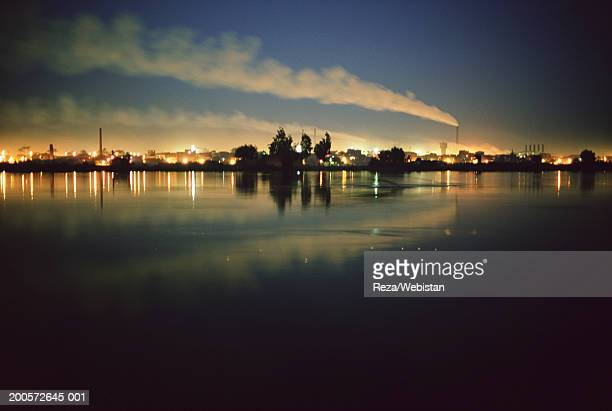 City with smokestacks on Nile river shore, night, Al Shobak, Cairo, Egypt