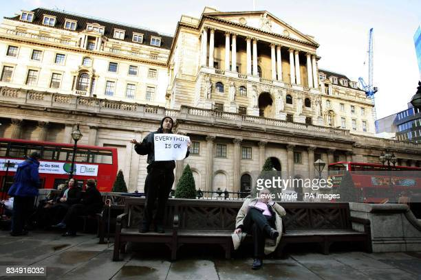 A city worker and a protester outside the Bank of England in London as interest rates are cut