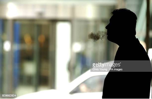 A City worker exhales on a cigarette outside his office near the London Stock Exchange as reaction spreads to Gordon Brown's budget As expected...