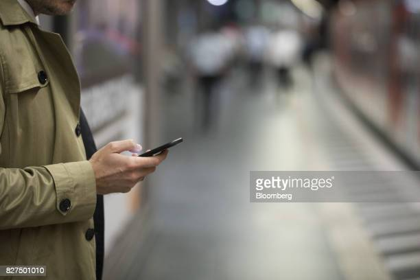 A city worker looks at his smartphone on the platform at Taunusanlage SBahn underground railway station in Frankfurt Germany on Monday Aug 7 2017...