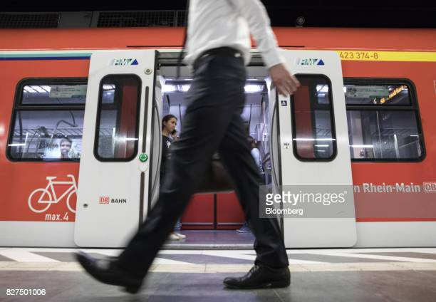A city worker passes a Deutsche Bahn underground train as it stands at a platform during the morning rush hour commute at Taunusanlage SBahn...