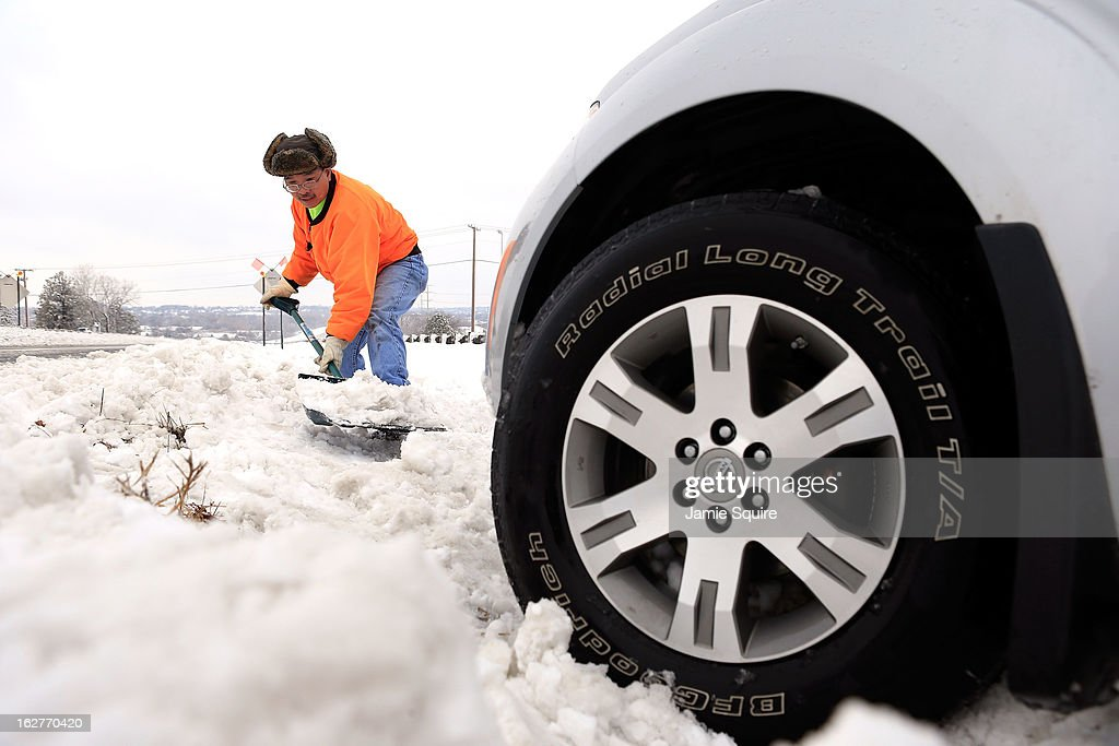 City worker Thuan Tran helps dig out a stranded motorist after the area is hit by a snowstorm on February 26, 2013 in Overland Park, Kansas. This is the second major snowstorm the midwest has seen this week dropping a half-foot or more of snow across Missouri and Kansas and cutting power to thousands...