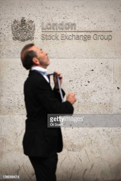 A city worker ties his tie as he walks past the London Stock Exchange on September 22 2011 in London England Share prices on world stock markets have...