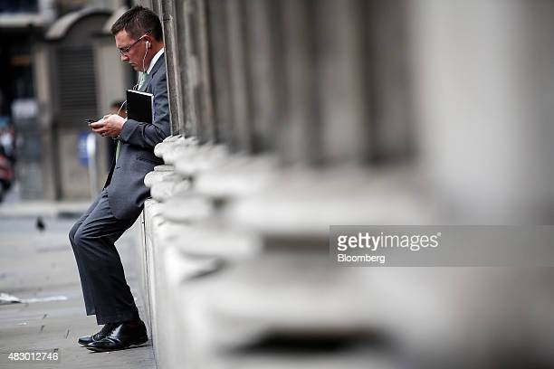 A city worker uses his mobile handset as he sits between the stone columns outside the Bank of England in the City of London UK on Wednesday Aug 5...