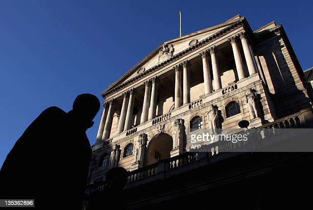 A city worker walks past the Bank of England in central London on December 9 2011 British Prime Minister David Cameron said Friday he took a 'tough...
