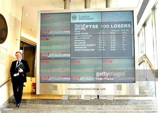 A city worker walks past the financial screen at the London Stock Exchange showing the FTSE 100 losers after the attack on Iraq March 20 2003 in...